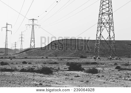 Desolate Infinity Of The Rocky Hills Of The Negev Desert In Israel. Electrical Power Lines On Pylons