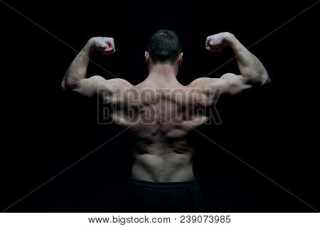 Bodybuilder With Fit Torso, Back View. Man Athlete Flex Arm Muscles. Sportsman Show Biceps And Trice