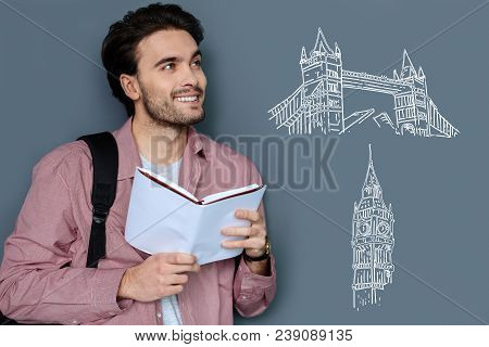 Pleasant Dreams. Cheerful Dreamy Student Standing With A Book In His Hands And Thinking About Travel