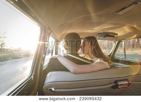 Young Wedding Couple Sitting Smiling Inside Retro Car. Just Married Embrace Is Hugging Inside Car. B