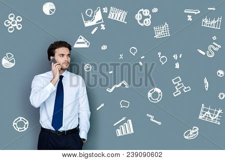Serious Talk. Clever Serious Businessman Looking Concentrated While Talking On The Phone