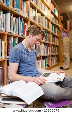 Portrait of a male student reading books while his classmate is reading in a library