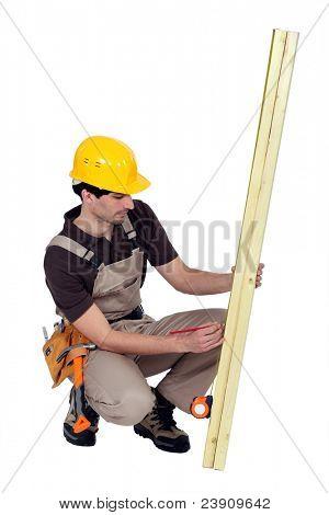 Man marking plank of wood