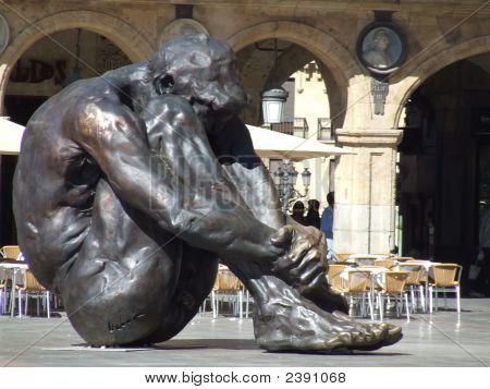 Epic Large Bronze Statue Of A Man Sits Curled Up In A Town Square In Salamanca, Spain