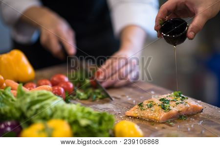 Chef hands preparing marinated Salmon fish fillet for frying in a restaurant kitchen