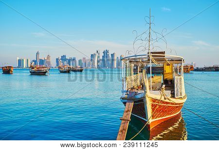 The Old Wooden Dhow Boat Is Slowly Rocking In Harbor Of Doha, Such Vessel Is Very Popular For Fishin