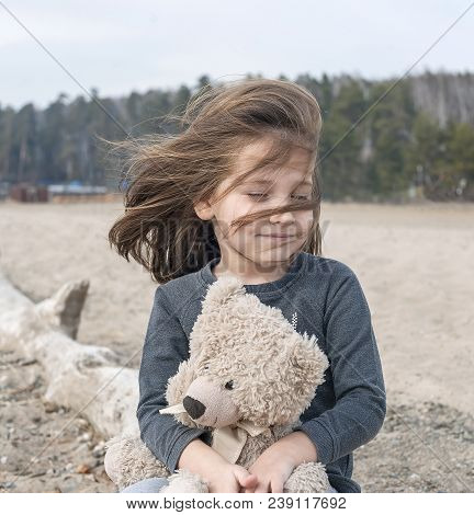 Little Girl Sitting On A Old Fallen Tree On The Beach, Hugs A Teddy Bear. Contentment, Drive, Enthus
