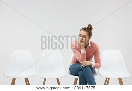 Horizontal Picture Of A Young Bored Female Sitting Alone In The Line And Waiting For Her Turn To Com