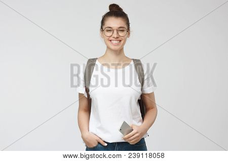 Horizontal Photo Of Young Beautiful European Woman Pictured Isolated On Grey Background Wearing Roun