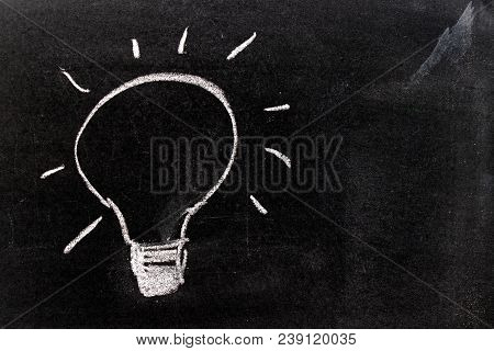 White Chalk Hand Drawing In Ligh Bulb Shape On Blackboard Background (concept For New Idea)