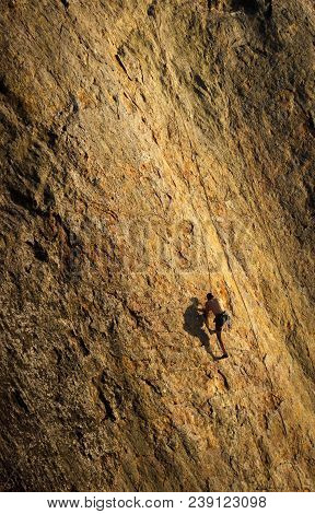 Male Rock Climber Struggles For His Next Grip On The Steep Cliffs Of Point Dume, Malibu, California