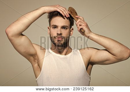 Man Brush Hair With Hairbrush On Grey Background. Macho With Bearded Face And Haircut In White Singl