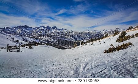 Panoramic View Of Steep Ski Trail With Snow-covered Sierra Nevada Mountain Range In The Background,