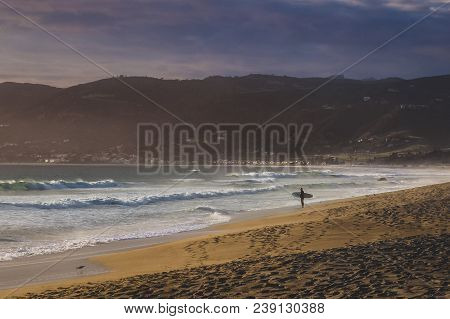 Male Surfer Standing On The Beach Holding His Surfboard At Point Dume State Beach With Colorful Clou