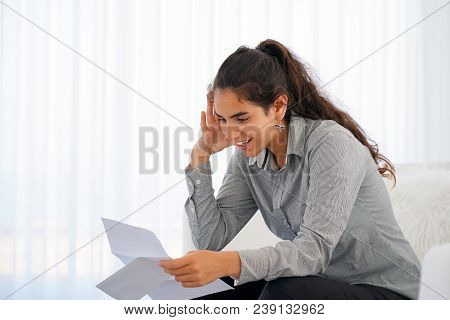 Happy Young Woman Enjoying Good News In Writing. The Girl Reads A Letter With Good News Sitting On T