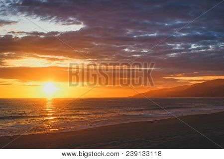 Beautiful Coastal Sunset On An Empty Point Dume State Beach With Colorful Clouds In The Sky And Sant