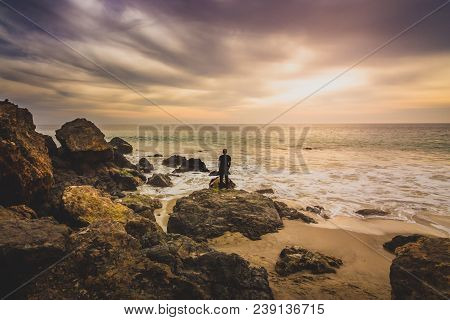 Man Standing On A Rock Formation Watching The Colorful Sky At Sunset As Waves Wash Onto The Rocky Sh