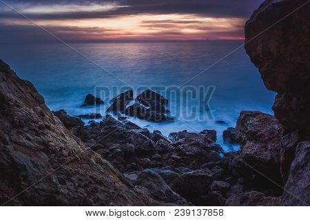 Long-exposure Photograph Of Silky Smooth Water Flowing Around Rock Formations After Sunset At Point