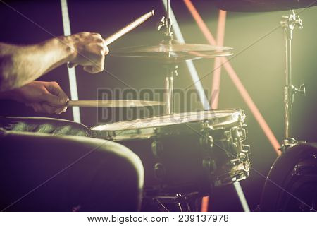 The Man Plays The Drums. On The Background Of Colored Lights.
