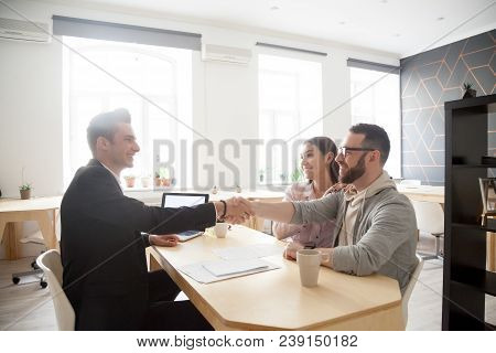 Happy Millennial Couple And Smiling Financial Advisor, Lawyer Or Realtor Shaking Hands At Office Mee