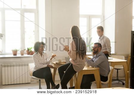 Smiling Multiracial Colleagues Talking Eating Pizza At Lunch In Office Room, Diverse Team People Enj