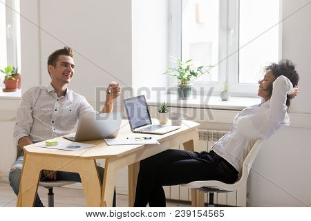 Millennial Multiracial Coworkers Chatting And Laughing In Office, Positive African And Caucasian Col