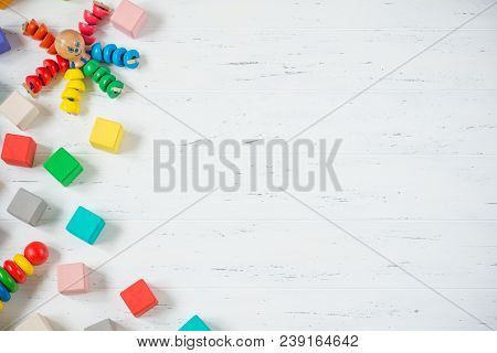 Kids Toys Frame Wooden Blocks, Octopus, Pyramidion On White Wooden Background. Top View. Flat Lay. C