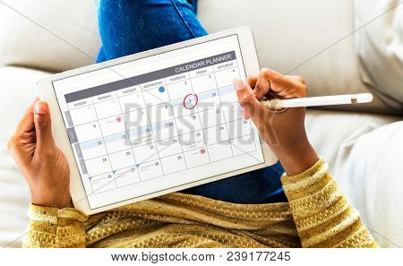 Woman checking calendar on digital tablet