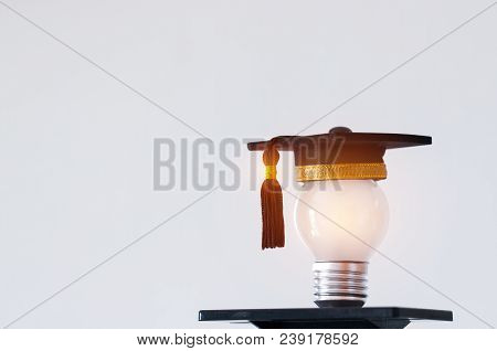 Education Or Graduate Study Creative Concept: Hands Holding Light Bulb With Graduated Hat On Gray Ba