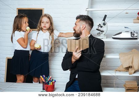 Back To School And Home Schooling. Teacher Man Read Story To Girls Eating Apple. Literature Lesson A