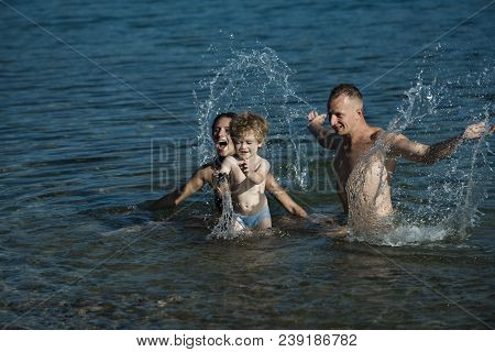 Love And Trust As Family Values. Mother And Father With Son Swim In Sea On Beach. Family Travel With