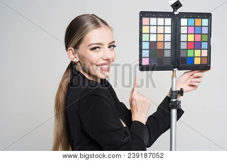 Young Photographer Pointing At Color Checker Card, While Working In Studio. Girl In Formal Suit Prep