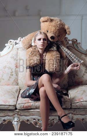 Young Spoiled Aristocrat Sitting On Vintage Sofa. Blond Lady Playing With Her Huge Teddy Bear.