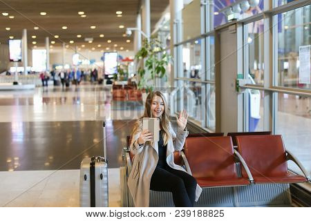 Female Person Making Video Call By Modern Tablet In Airport Waiting Room And Sitting Near Grey Valis