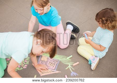 Little Sisters Draw With Color Chalk Outdoors. Chalk Drawings