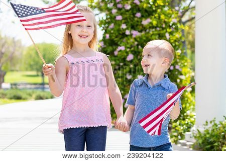 Young Sister and Brother Waving American Flags At The Park.