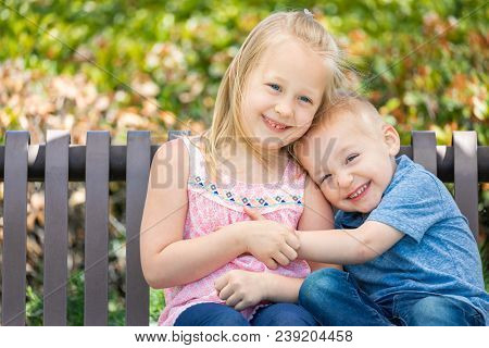 Young Sister and Brother Having Fun On The Bench At The Park.