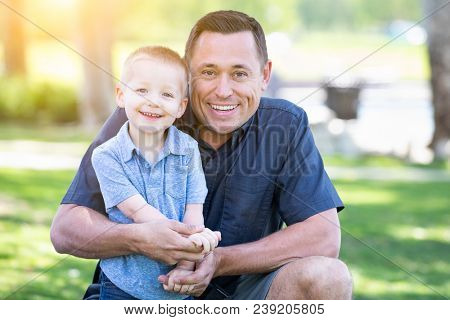 Young Caucasian Father and Son Having Fun At The Park.