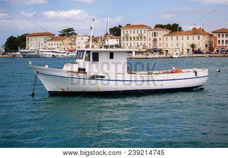 Small Fishing Boat In Mediterranean Harbor In Porec, Croatia