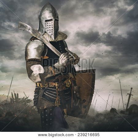 Knight In Armour On Battle Rise Under Stormy Sky. Knight With Sword In Battlefield.