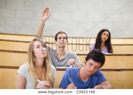 Student raising his hand while his classmates are taking notes in an amphitheater