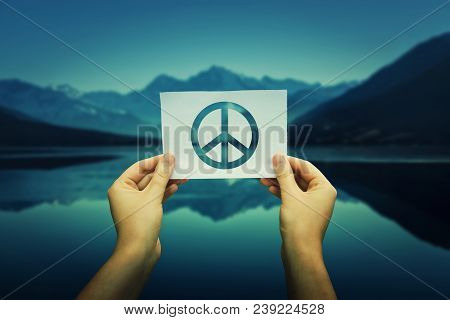 Close Up Of Woman Hands Holding A White Paper Sheet With Peace Symbol Over A Nature Background With