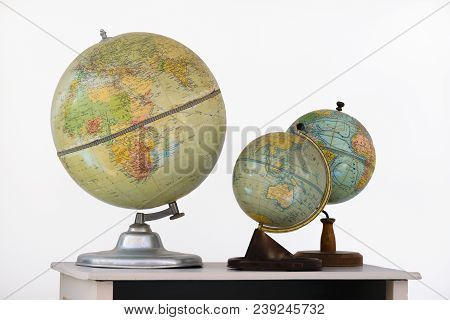 Three Terrestrial Globes On Top Of A School Table On White Background