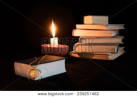 Still Life On Black Background With Stacked Books, Candle And Single Book On Foreground On Which Lay