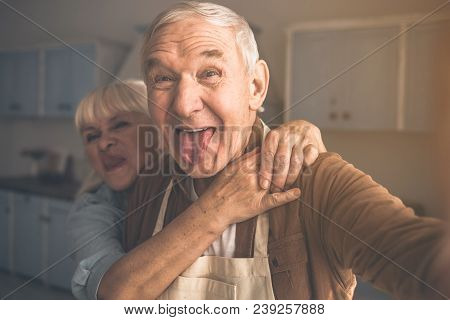 Portrait Of Joyful Senior Married Couple Having Fun In Cook Room. They Are Taking Photo Of Themselve