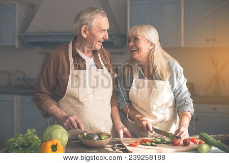 Portrait Of Happy Senior Loving Couple Making Salad Together In Cook Room. They Are Listening To Mus