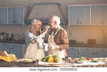 Affectionate Senior Married Couple Is Feeding Each Other By Sweet Pastry With Love. They Are Holding