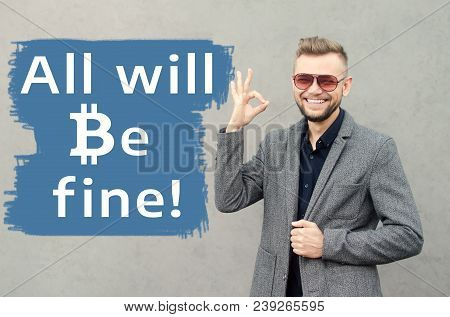A Smiling Attractive Man Against The Background Of The Wall On Which It Is Written All Will Be Fine.