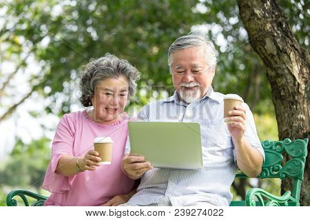 Senior People Using Laptop For Live Chat With Friend At Outdoor Park. Elder People Using Laptop With