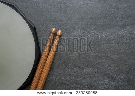 Drum Stick And Drum Pad On Black Table Background, Top View, Music Concept